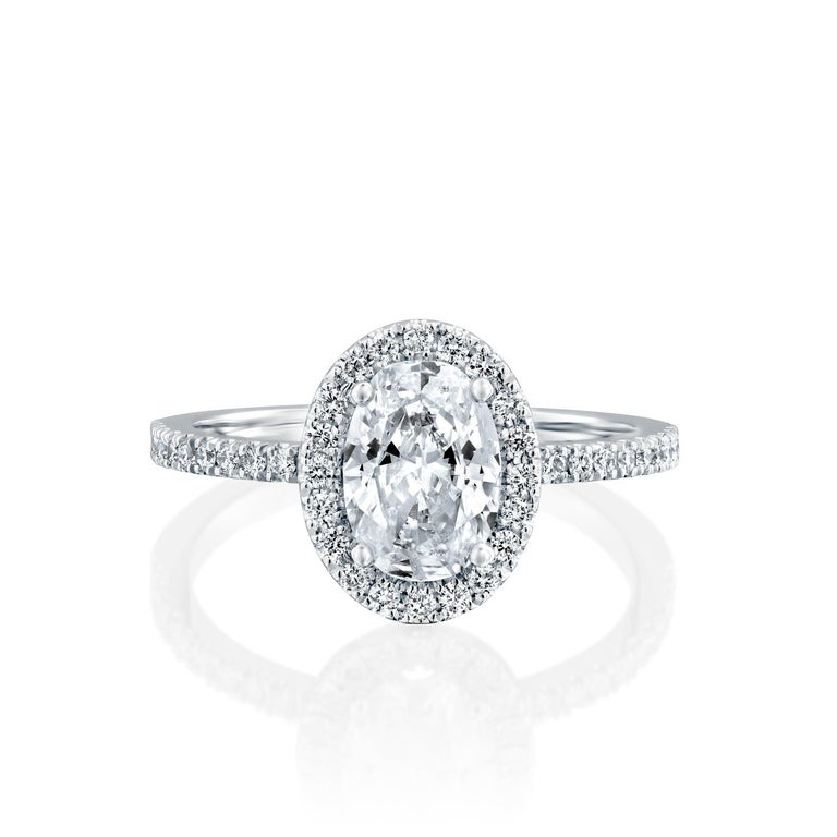 This impressive ring features a solitaire GIA certified oval diamond. Center stone is 2 carat oval cut 100% eye clean natural diamond of F-G color and VS2-SI1 clarity and it is surrounded by smaller natural round diamonds of 0.5 total carat weight.