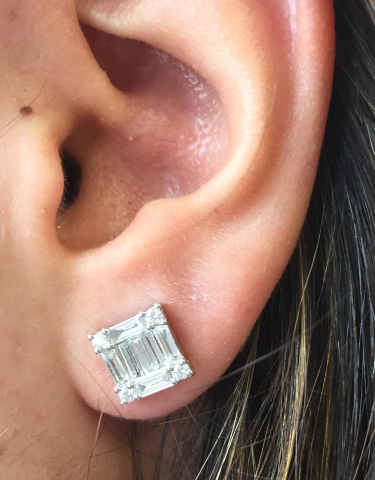 This Princess Cut cluster earrings, create the illusion of a single stone. It's a classic look that you can wear on every occasion. This piece is a mosaic of baguette and rounds diamonds.  The earrings are F color and VS1-VS2 clarity. Excellent Cut