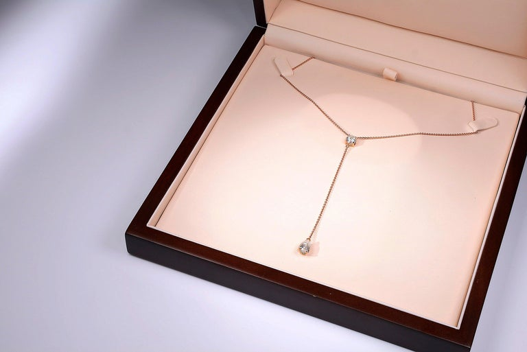 Timeless contemporary 18 karat rosé golden necklace featuring a 1.00 carat certified E/VVS1 round cut moissanite and a 1.50 carat certified E/VVS1 pear cut moissanite. Total length of the necklace is 40 cm and a drop of 8 cm. Beautifully handmade