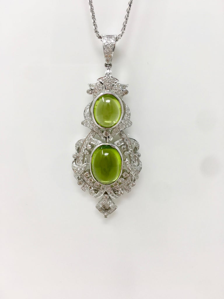 This beautiful custom handmade creation by Moguldiam Inc features a pair of earrings and a pendant. The diamond weight is 2.52 carat with VS clarity and GH color and peridot weight is 17.34 carat. The gold weighs 31.900 grams. The measurements on