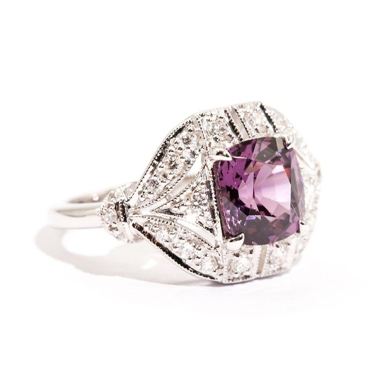Forged in 18 carat white gold is this art deco inspired ring that features a gorgeous 2.54 carat bright pinkish purple cushion cut natural spinel complimented by a total of 0.45 carats of sparkling round brilliant cut diamonds. We have named this
