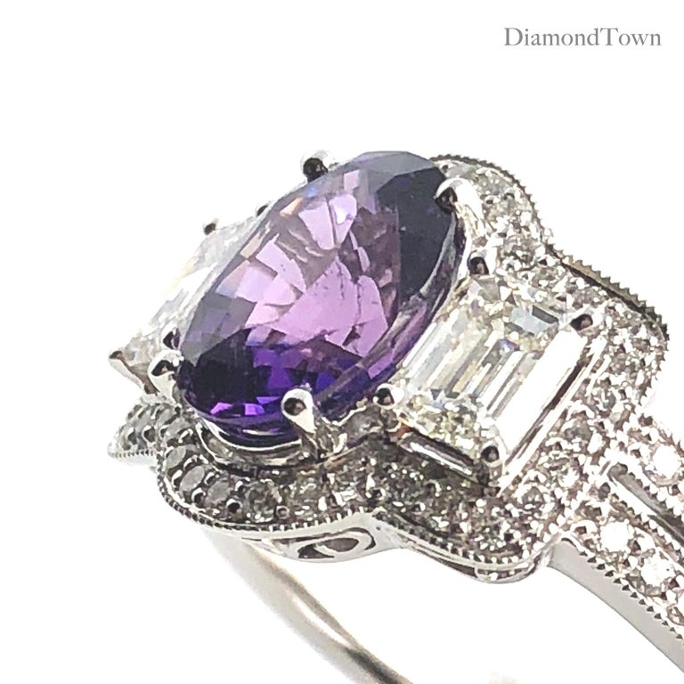 This beautiful ring has an exotic 2.55 carat oval cut Bicolor Sapphire center, flanked by two baguette diamonds and encircled by a halo of round diamonds. Additional diamonds trace down the side shank, bringing the total diamond weight to 1.16