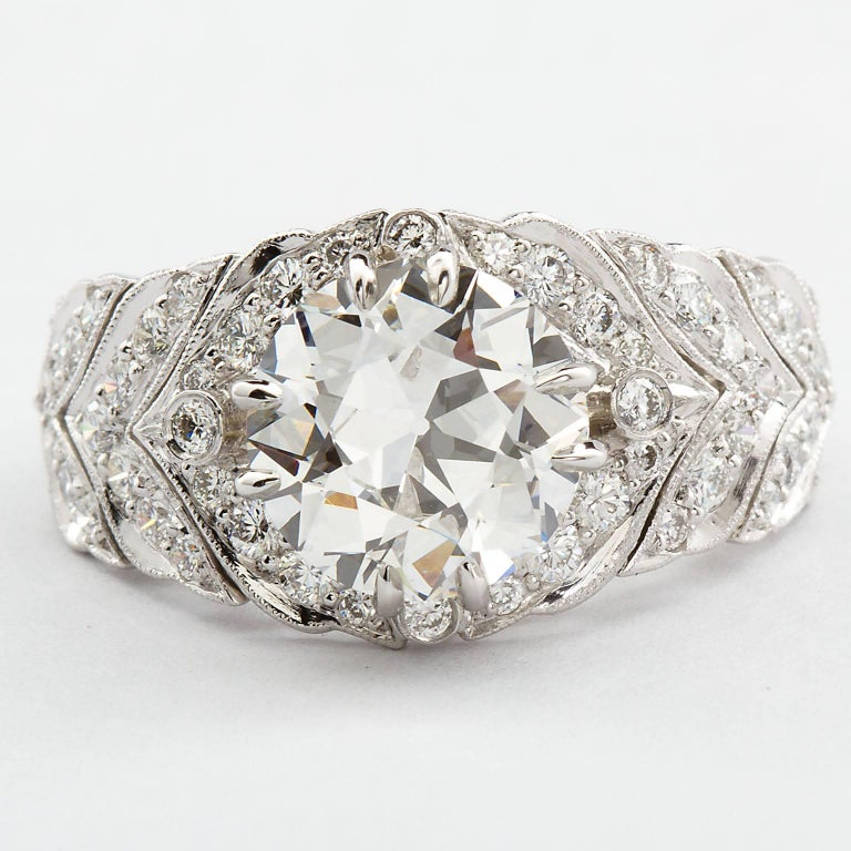 A very fine 2.59 carat Old European cut diamond F color VVS2 clarity set in a remarkable  ring with a flexing back. The ring shoulders feature Art Deco fine diamond inlay and millgraining design until half way down where the ring part becomes an