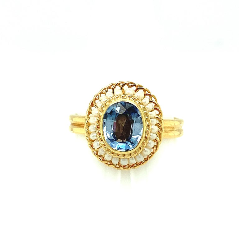 A bright and lively 2.61 carat oval blue sapphire is featured in this beautiful 18k yellow gold cocktail ring. This lovely ring was made by hand using the intricate art of filigree, using fine 18k yellow gold wire to thread and wrap seed pearls into