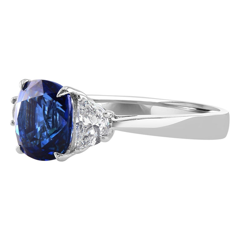 This beautiful ring features a 2.66 carat cushion blue sapphire, set between two half moons, 0.55 carat total weight.   Introducing a gorgeous colored gemstone engagement ring that will surely be a one of a kind look for any lucky lady. If you are