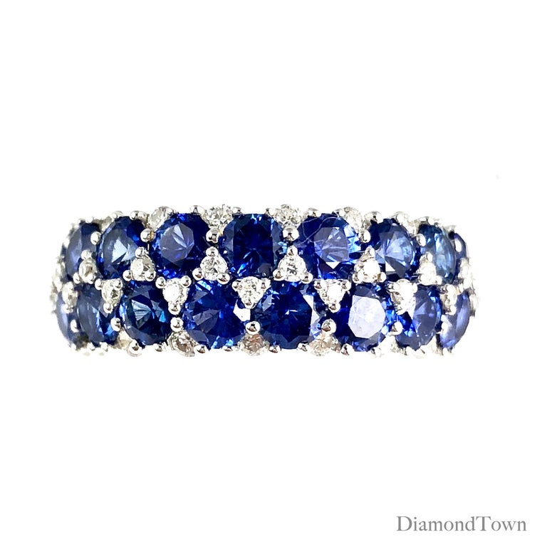 This gorgeous handcrafted ring features 17 round vivid blue sapphires tucked among 0.44 carats white diamonds. The layered design extends across the full width of the band.  This ring can be professionally sized to your specification, at no charge,