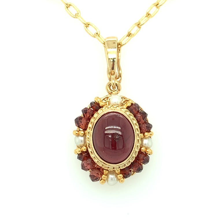 This pendant features a beautiful oval garnet cabochon in an intricate design of handmade 18k yellow gold filigree. The richly colored garnet is bezel set and framed by a halo of seed pearls and delicate garnet beads that have been hand strung on