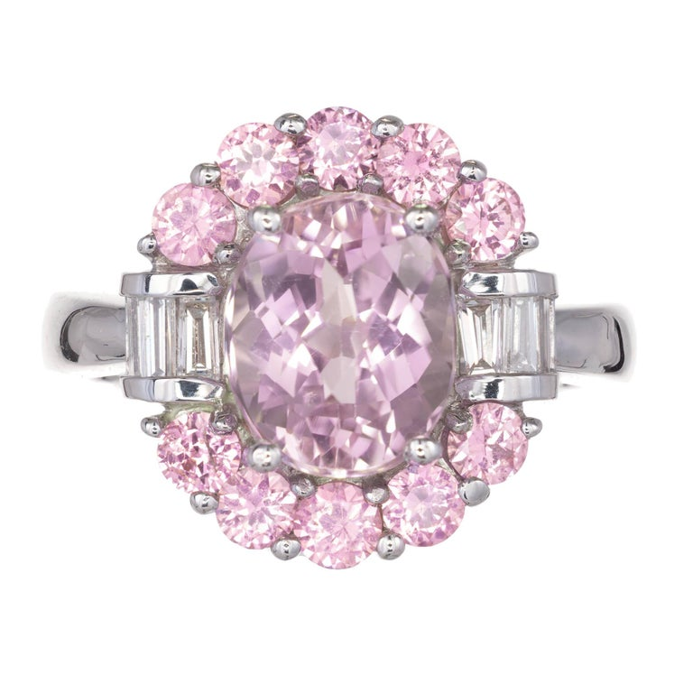 Light lavender oval faceted Amethyst set with round pink sapphires above and below by baguette diamonds in a 14k white gold setting.  1 oval pale amethyst Approximate 2.75 carats 10 round pink sapphires Approximate 1.50 carats 6 baguette G-H VS