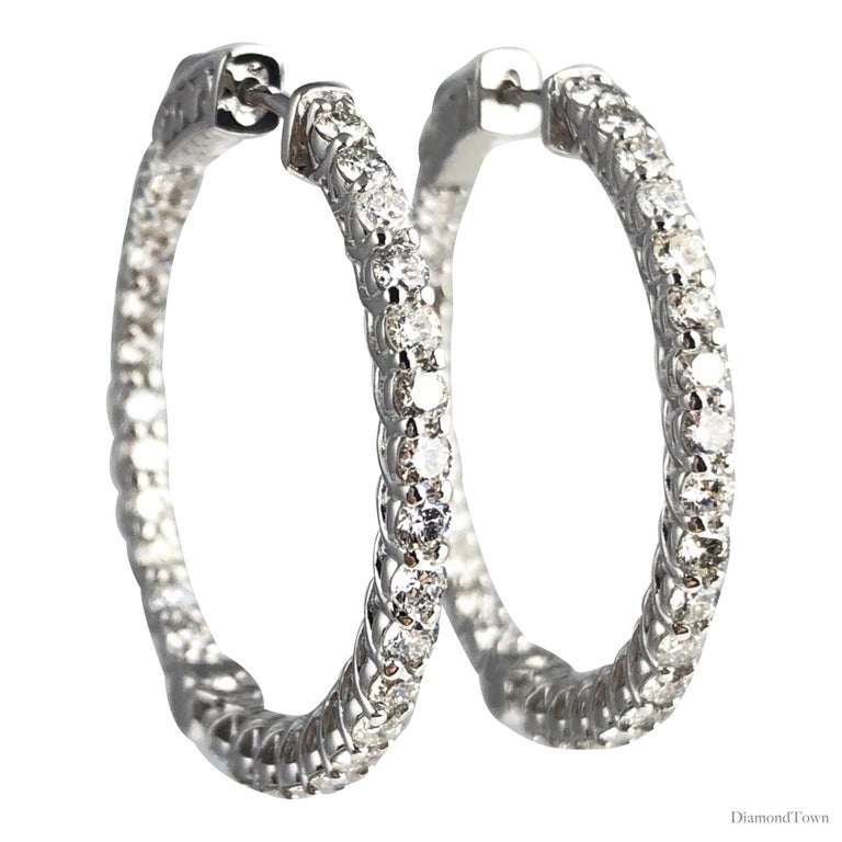 This lovely round hoop earrings feature 58 2.3mm round diamonds in an inside-outside pattern adorning the front-facing areas.  58 round diamonds total 2.76 carats. Set in 14k White Gold. The earrings close with a click-lock feature (see