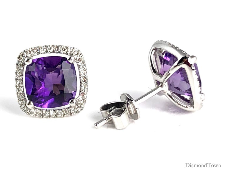 These stunning halo stud earrings feature 2.76 carats Fine Amethyst, surrounded by a halo of round white diamonds.  Center: two cushion cut Fine Amethyst stones total 2.76 carats Diamond Halo: 64 round diamonds total 0.18 carats Set in 14k White