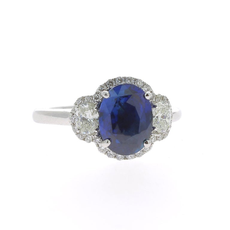 An amazing Blue Sapphire Ring flanked on each side by a single Oval Diamond and surrounded by an halo of Round Diamond. The total weight of the Sapphire is 2.77 Carats, the gemstone is certified as a Blue Standard Heat Only Sapphire.  The Oval