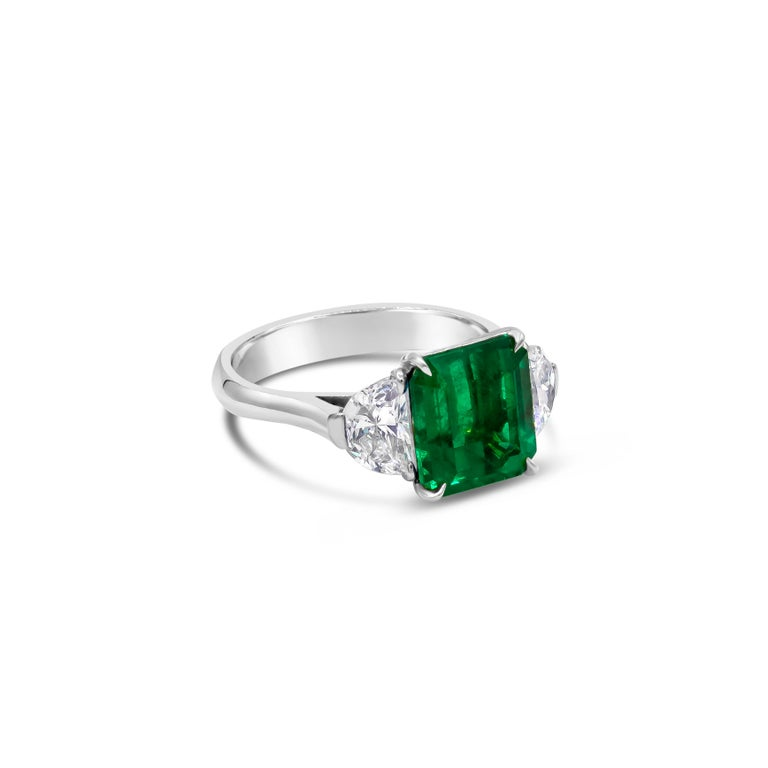 Showcases an emerald cut, green Colombian emerald weighing 2.77 carats, flanked by two brilliant half-moon diamonds weighing 1.10 carats total. Elegantly set in a polished platinum composition.