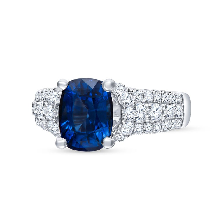 Beautifully placed 2.77 carat cushion cut natural blue sapphire (GIA Certified) centered in a 3-Row diamond band going halfway. The ring is made into a size 5 and may be resized to larger or smaller upon request.   Diamond Quality: F-G color,