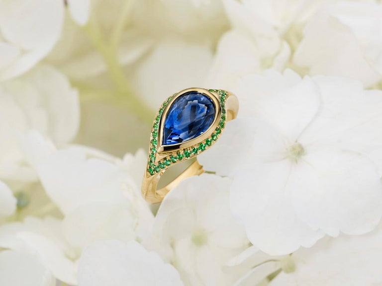 A 2.79 ct Ceylon sapphire, pear shaped; encircled with the finest tsavorites. A combination of old world techniques that only a hand made piece of fine jewelry will offer- hand carved wax mold, which is cast and then expertly hand set with pavé