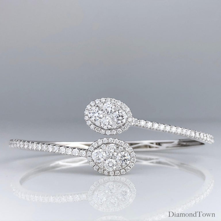 This stunning bangle bracelet features two clusters of round diamonds, surrounded by a halo of additional round diamonds, which also extends down the front face of the bangle. The bangle opens by smooth hinge on the reverse side.  Set in 18k White