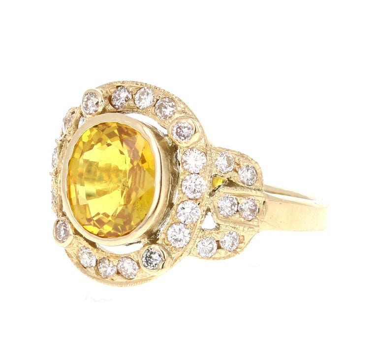 Art Deco Inspired Yellow Sapphire and Diamond Ring!  This ring has a 2.25 Oval Cut Yellow Sapphire in the center of the ring and is surrounded by a cluster of 30 Round Cut Diamonds that weigh 0.63 carats. The clarity and color is VS2/H.  The total