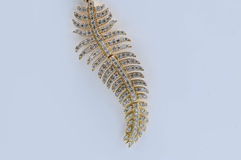 The elongated feather entirely decorated with round micro-pav diamonds weighing approximately 2.90 carats, hinged bail, mounted in 18k pink gold, together with a pink gold plated trace linking chain,   Condition Report: Dimensions: pendant 133 mm