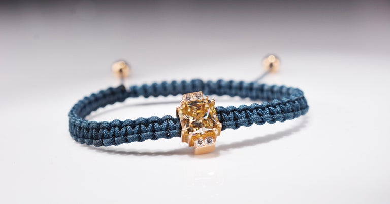 Contemporary unisex macramé bracelet, featuring a 2.92 carat Radiant cut fancy light yellow Moissanite center stone set in 18 karat rosé gold accompanied by 0.24 carat (4 x 0.06ct) F/VS round diamonds. The ends on the bracelet are also made out of