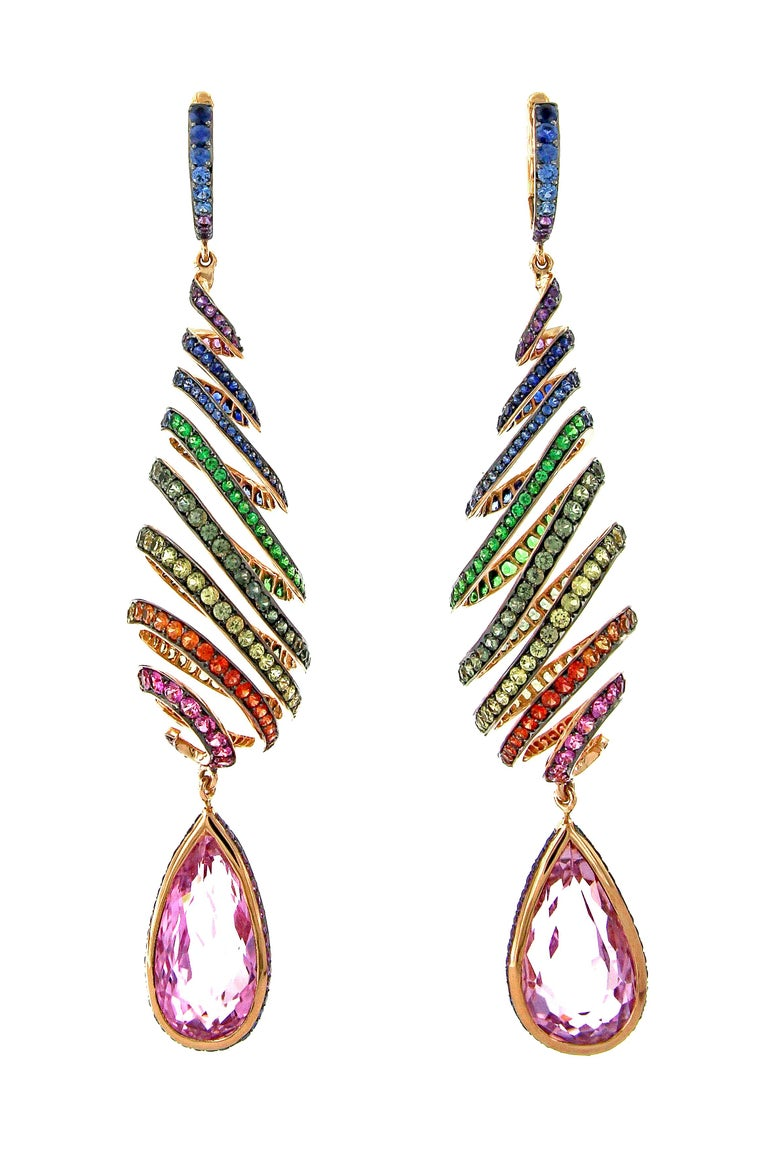 This pair of long 18k pink gold and coloured gemstone earrings are the heart of a three piece set. The teardrop spiral design was carefully and expertly crafted to ensure strength and moveability. The coloured stones, including multi-coloured