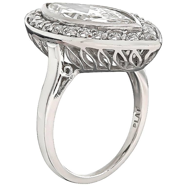 This unique platinum engagement ring inspired from the Art Deco era, is centered with a sparkling marquise cut diamond that weighs 2.95ct. graded H color with SI1 clarity. The center diamond is accentuated by dazzling old mine cut diamonds that