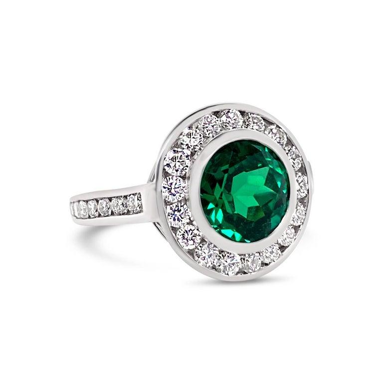 2.99 Carats Vivid Green Emerald Bezel Set with 1.14 Carats of Diamond accents. Set in Platinum.