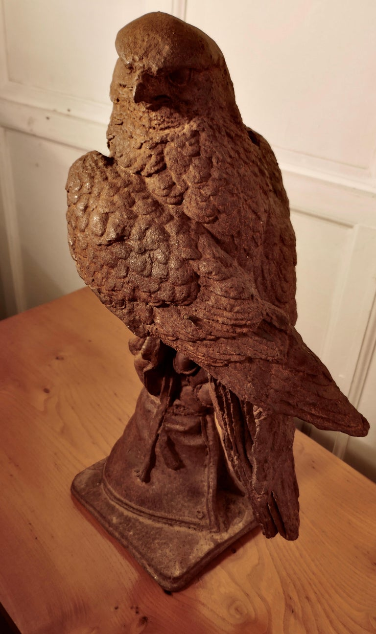 Tall weathered cast iron statue of a falcon on a gloved hand   This wonderful statue has a good aged patina it shows a falcon held on a gloved hand  This piece has the most superb detailed casting, the feathers, the stitching on the glove but