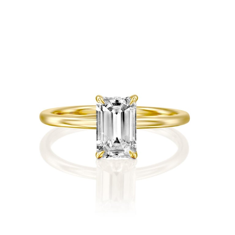 This breathtaking ring features a solitaire GIA certified diamond. Ring features a 3/4 carat emerald cut 100% eye clean natural diamond of F-G color and VS2-SI1 clarity. Set in a sleek, 18K yellow gold, solitaire ring with a 4-prong setting, this