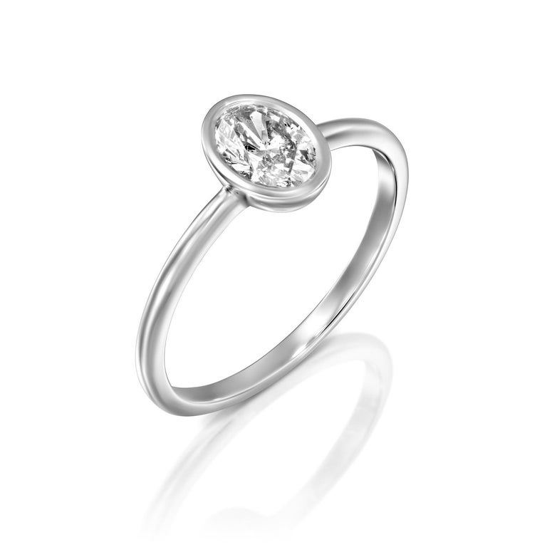 Classic and timeless oval GIA certified diamond engagement ring. Ring features a 3/4 carat oval cut 100% eye clean natural diamond of F-G color and VS2-SI1 clarity. Set in a sleek, 18K white gold, solitaire ring with a bezel setting, this fantastic