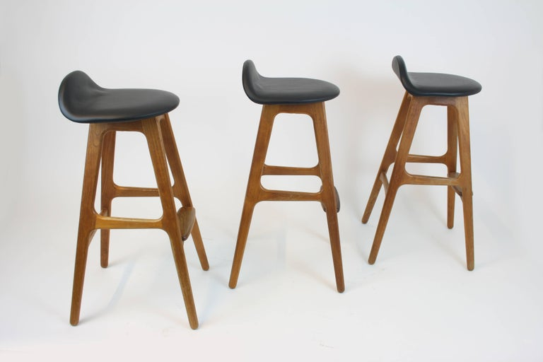 Three bar stools by the Danish designer Erik Buch (pronounced: Buck), manufactured by the Odense furniture factory in the late 1950s. Our variant of the stool is made of solid teak wood and its seating newly upholstered with black leather. Their