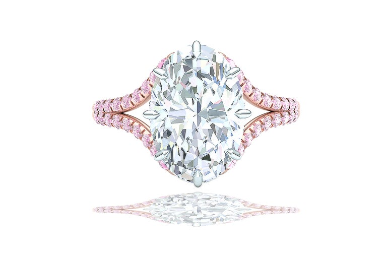 This stunning oval cut brilliant diamond is GIA certified and has a color and clarity of F-VS2.  The center stone is encased by over .50 carats of white round brilliant diamonds which are E-F VS.  The head of this ring is cast from platinum and sits