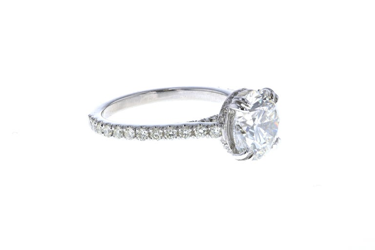 This 3 carat diamond engagement ring is crafted in platinum and contains a round diamond (3.10 total carat weight, I color, SI1, clarity) surrounded by 76 round diamonds (0.54 total carat weight, I color, SI clarity) and features a hidden diamond
