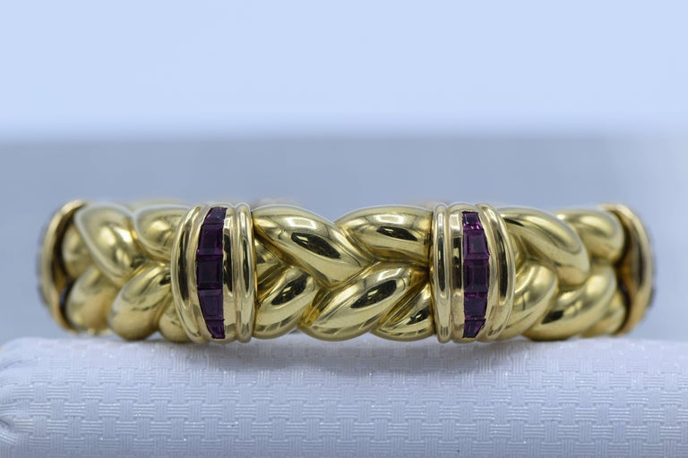 The penannular slightly spring-mounted braid motif with a quartet of fluted stations accented by channels of rubies, in 18k gold, inner circumference 6 1/8 inches  Dimensions: 16 mm   Rubies: medium dark pinkish red