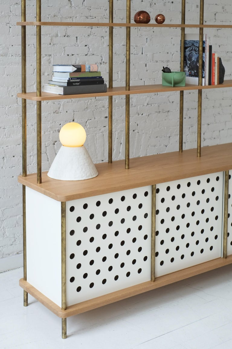Consistent with the Strata collection, the new Strata sideboard is designed to be modular in order to create versatile configurations tailored to your needs. Shown with brass rods, walnut shelving and powder coated aluminum sliding doors, all
