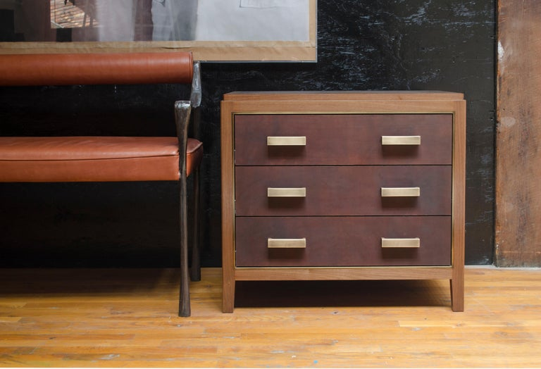 Solid walnut construction featured with three drawers. Wood options also include oak or wenge. Configuration options also include single or two drawers with open shelving. Brass trim and hand-dyed saddle leather drawer fronts and blotter. Leather