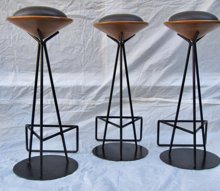 Three wrought iron bar stools from Palm Springs, circa 1960s.  The seat supports are laminated oak that are lathe turned which hold the seat cushion. The bar stools are in excellent condition.