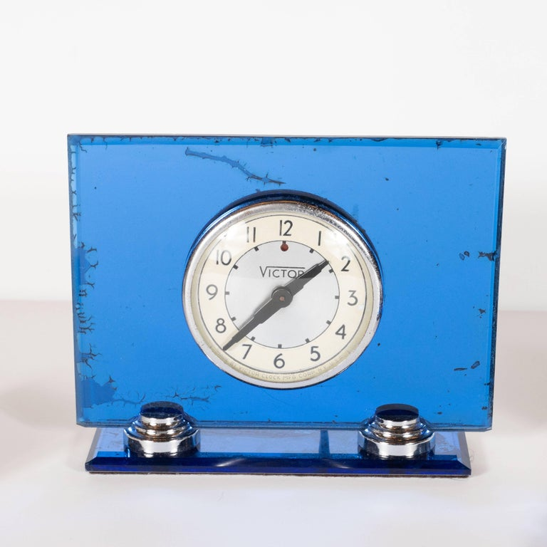 This sophisticated Art Deco Machine Age desk set was realized by the celebrated American maker, Victor, circa 1930. It features a inkwell/pen holder, a blotter and a clock. The inkwell offers a square body composed of translucent Lucite with a