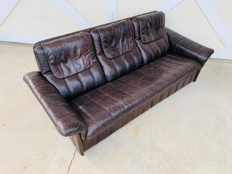 Vintage 3-seat sofa upholstered in brown leather designed and manufactured in Switzerland by De Sede.  The piece is all original and is in good vintage condition.  Measurements: 79 inches wide x 33 inches deep x 31 inches high x 16.5 inches