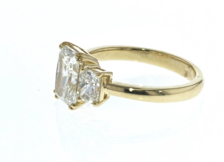 This diamond ring is crafted in 18k yellow gold, contains a Radiant Cut Diamond (1.53 total carat weight, G color, VS2 clarity,  surrounded by 2 matching Radiant Cut Diamonds (0.67 total carat weight, G color, VS clarity). With a raised profile and