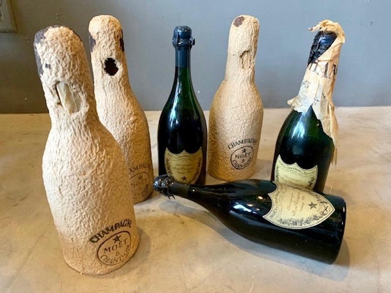 Three bottles of Dom Perignon or Moet et Chandon. Two are dated 1952 and one 1955. Include original tissue paper and bottle covers. I assume these wouldn't be tasty to drink. Interesting vintage find and great for a bar.