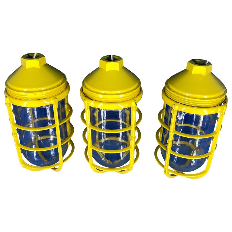 Set of 3 salvaged vintage Industrial three-light blast proof ceiling fixtures, newly powder-coated in bright sunshine yellow.