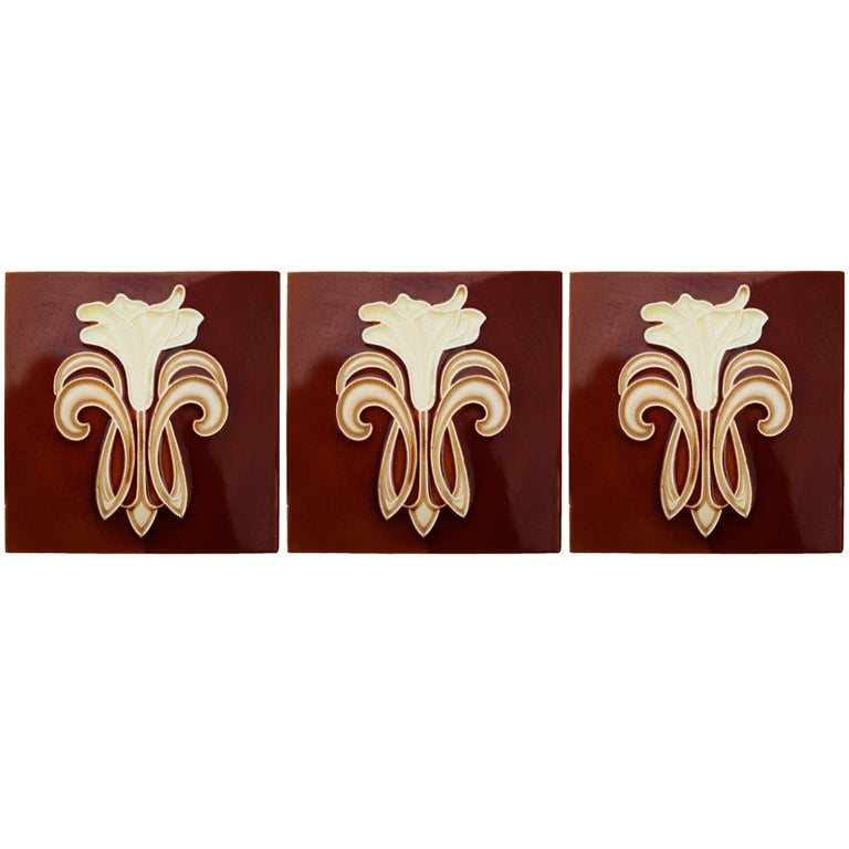 Recently lifted from its original home, a set of antique tiles from the early 20th century. With a beautiful stylized design of a lily. Manufactured by Gilliot Fabrieken te Hemiksem.  Size each tile: inches 5.9 inches (15.1 cm) width x 5.9 inches