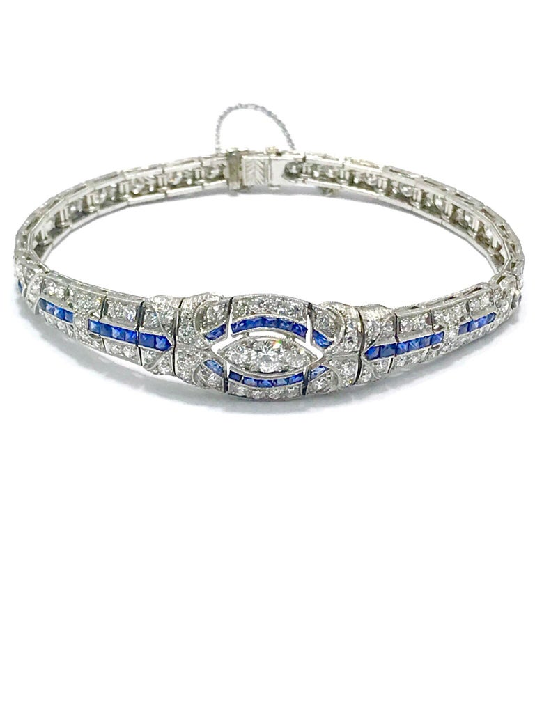 This is an absolutely gorgeous Art Deco diamond and sapphire platinum bracelet.  The bracelet contains 97 round diamonds for a total weight of 3.00 carats, accented by channel set french cut sapphires in hand crafted filigree beaded edge platinum.