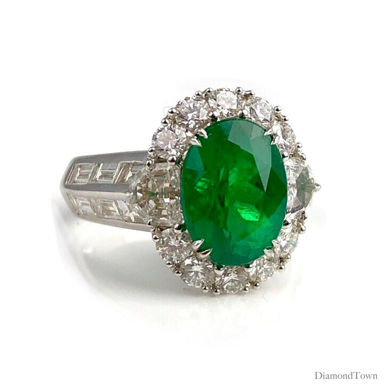 (DiamondTown) This ring sparkles with a 3.00 carat Colombian Emerald center, surrounded by a halo of white diamonds and additional diamonds extending down the side shank. (Total diamond weight 2.50 carats.)  Set in 18k White Gold.  Many of our items