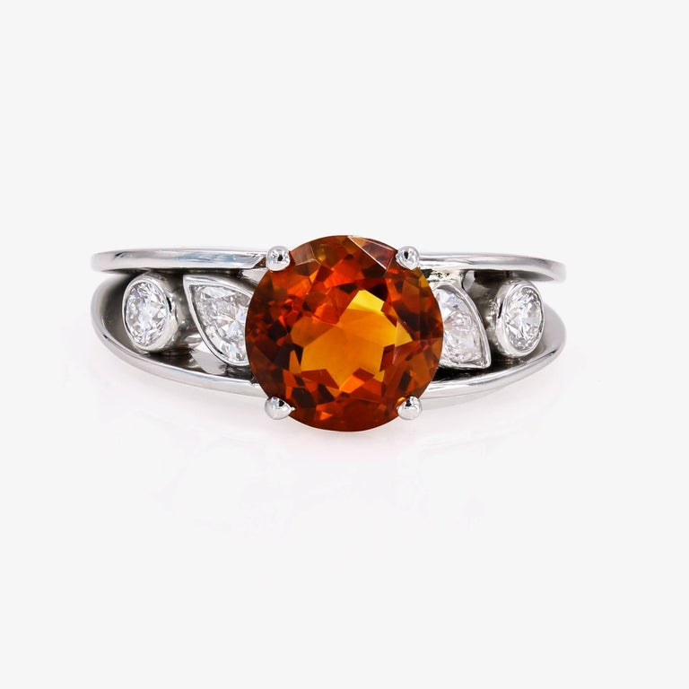 This vibrant ring contains a 3.00cts. round center citrine of orange-brownish color. There are 2 pear shape diamonds on the sides=.39ct. t.w. and 2 ideal cut round diamonds=.24ct. t.w. The ring is set in platinum. (diamonds are G in color and VS