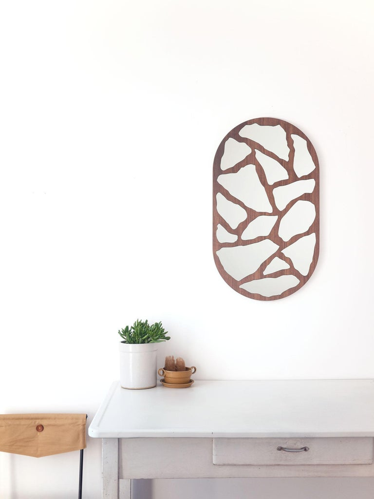 An adaptation of Trueing's original #3000 mirror in marble and concrete, this updated version is rendered in warm walnut. Crafted with an enlarged and revised terrazzo pattern, mirror segments stand in for marble, resulting in an restrained, yet