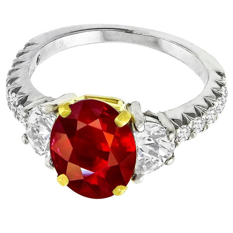Made of platinum and 18k yellow gold, this ring centers a lovely oval cut ruby that weighs 3.02ct. The center stone is accentuated by sparkling half moon and round cut diamonds that weigh approximately 0.70ct and 0.80ct respectively. The color of