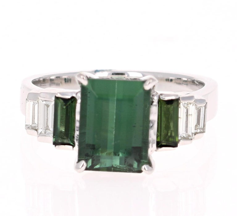 A unique beauty that is sure to be a rare and gorgeous design! Very much inspired by the articulate designs of the art-deco era.  This stunner has a Emerald Cut Green Tourmaline that weighs 2.41 Carats. Adjacent to the tourmaline are 2 Baguette Cut