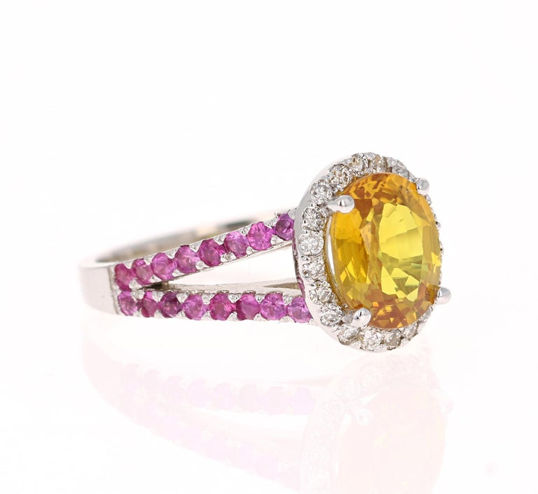 This beautiful ring has an Oval Cut Yellow Sapphire that weighs 2.17 Carats. It is surrounded by 22 Round Cut Diamonds that weigh 0.24 Carats. (Clarity: VS, Color: H) and it has Pink Sapphires on its shank that weigh 0.65 Carats. The total carat