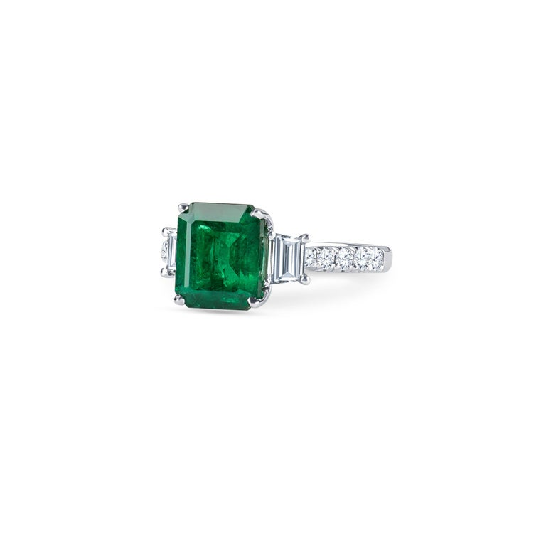 3.06 Carat  natural emerald (AGL certified) in emerald cut with 0.96 carats total weight of trapezoid step-cut & round brilliant diamonds, set in 18K white gold.  Ring size 6, may be resized to larger or smaller upon request.