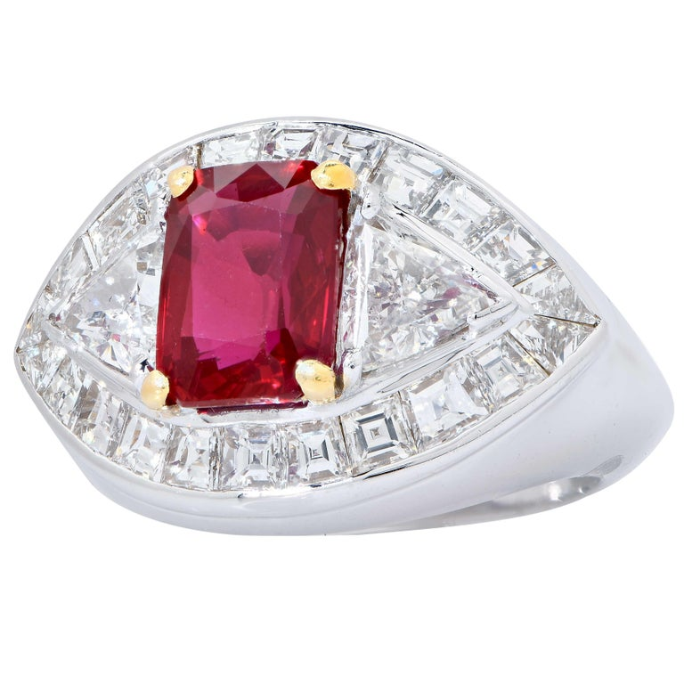 18 Karat White Gold Ruby and Diamond Cocktail Ring Featuring a Navette Shaped Panel Center Set with An Emerald Shaped Mix Cut Ruby Weighing 3.09 Carats Accompanied By An American Gemological Laboratory (AGL) Colored Stone Origin Report Dated 24